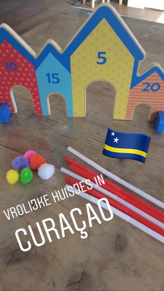 Blaas met een rietje het balletje door een deur van de gekleurde huisjes in Curaçao